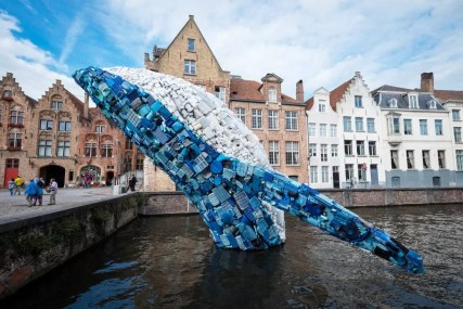 Triennial artwork of humpback whale in plastic jumping out of a Bruges canal