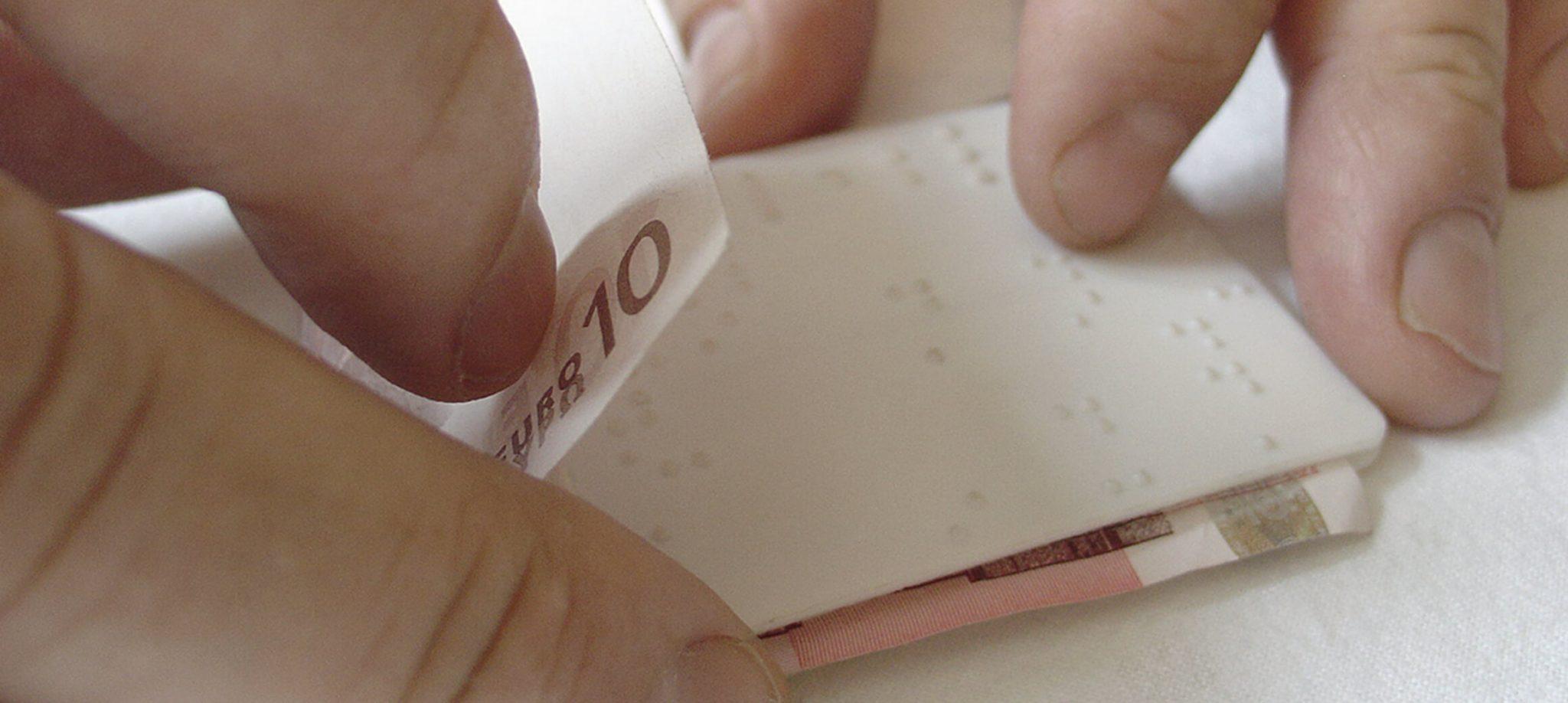 Eine Hand die gerade mittels Cash Test einen 10€ Schein erfasst