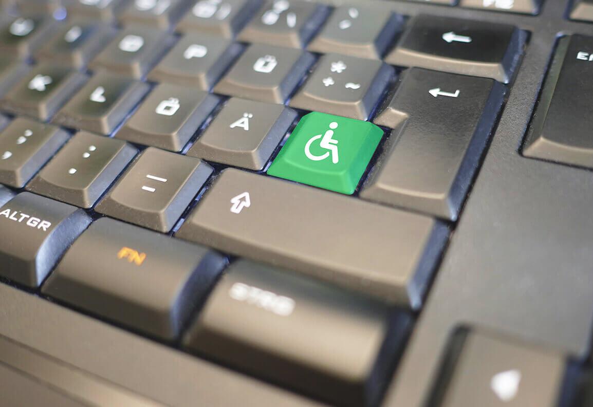 Foto einer schwarzen Tastatur. Eine Taste ist grün. Darauf befindet sich das Symbol für RollstuhlfahrerInnen.