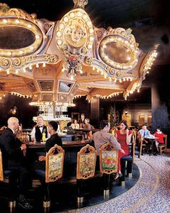 With lights, mirrors, and fanciful jester faces, it is part Merry-go-round and part Mardi Gras float. Carousel Bar by Chris.j.cook (Own work), via Wikimedia Commons.