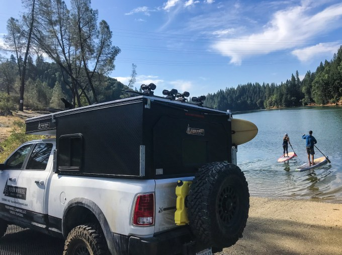 2 people paddle board while their pop-up camper sits on the shoreline.