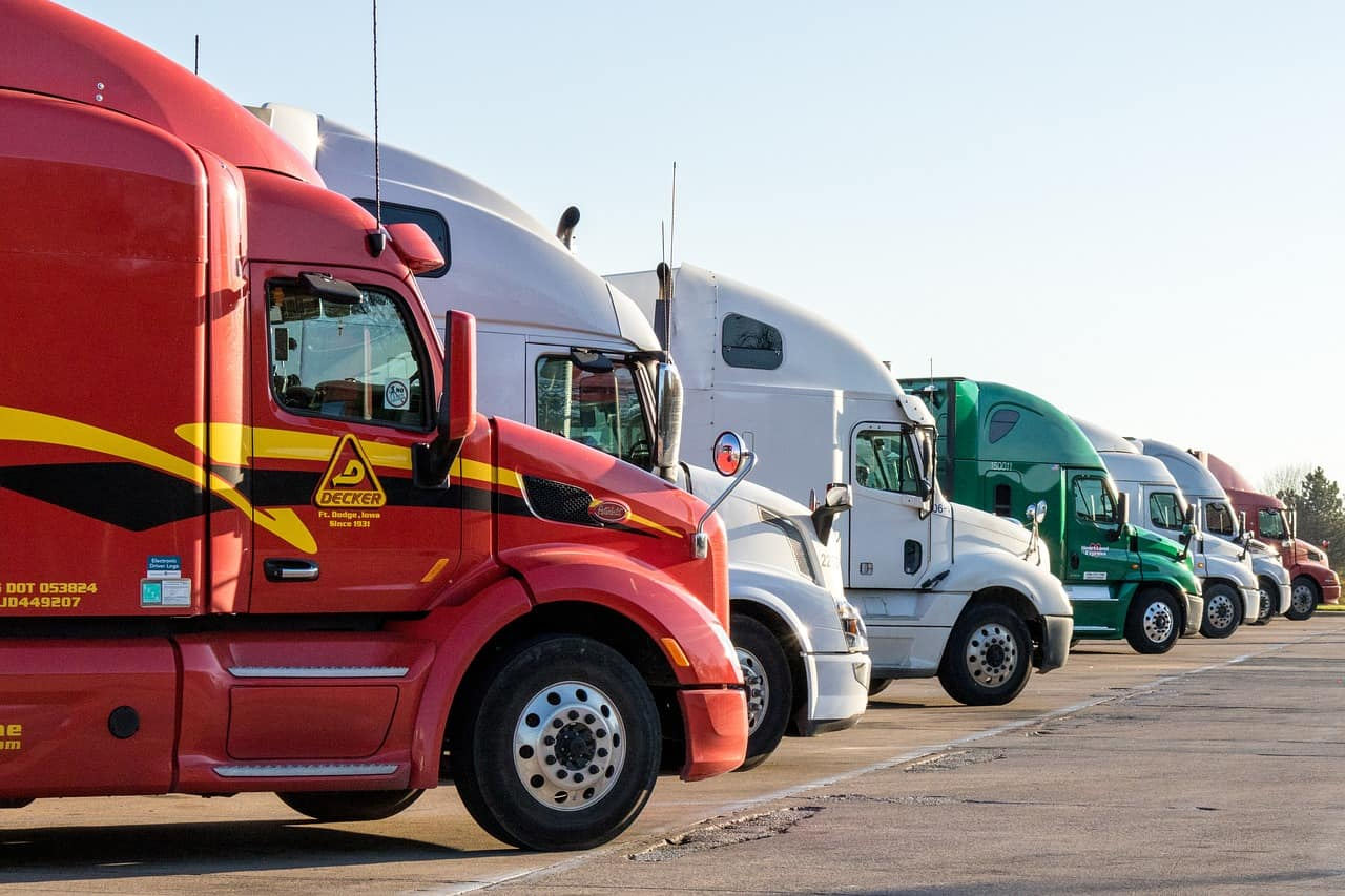future of truck driving jobs - lineup of big rigs pointed towards the horizon