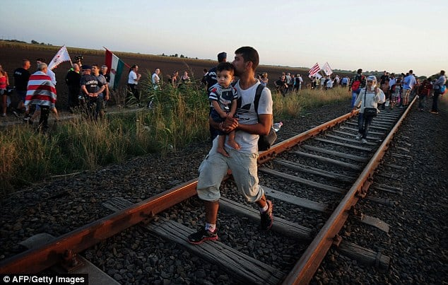 AFP/Getty. A man carries a young child into Hungary at the Serbian border as the national right-wing party Jobbik demonstrate against refugees.