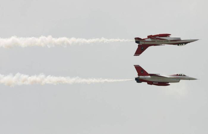Members of the Republic of Singapore Air Force Black Knights aerobatic team perform during a show at a military airport in Bangkok