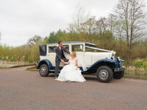 The couple with the wedding car