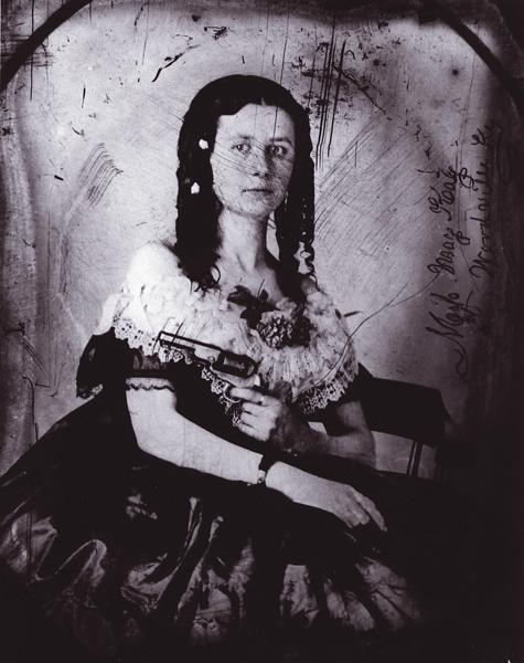 Due to its small size, the 1849 Colt was popular as a hideout gun with people from all walks of life. It could easily be hidden in a man's jacket pocket or, as this 1860s ambrotype reveals, within the voluminous folds of a female dress. Of Woodville, Kentucky, Miss May Kay's tiny hands make the Pocket '49 appear to be large.– Courtesy Herb Peck, Jr. Collection –