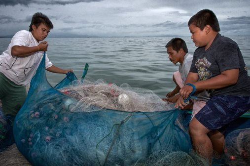Harit (left), Panit and Muussin prepare to lay out one of the several massive nylon fishing nets used in their profession. They will spend at least a couple of hours just laying out a string of nets that will stretch for several kilometers in the Gulf of Thailand.