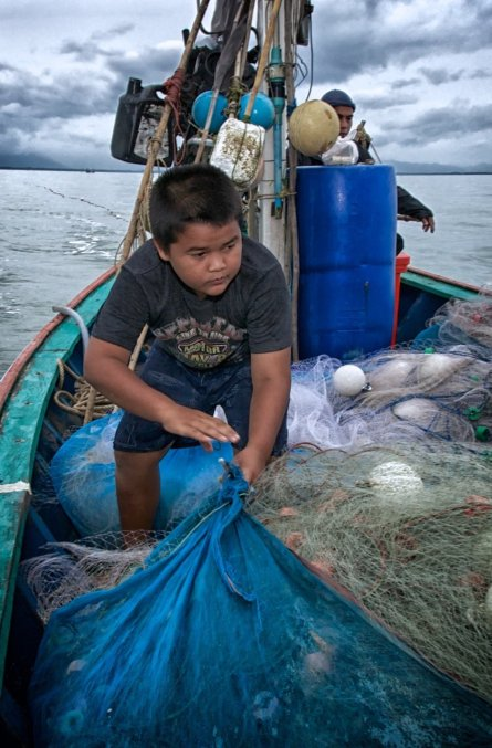 Muussin helps prepare a nylon fishing net for deployment as his father maneuvers to just the right spot.