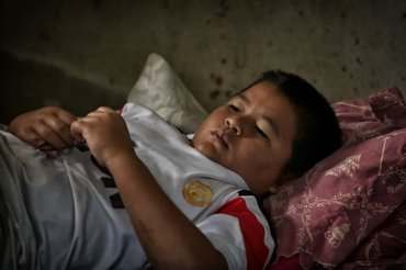 Muussin rests after a hard night's work. He doesn't go to school this year; his father pulled him out to work on the boat, which Muussin much prefers. He catches naps and relaxes in the afternoons before going out on the boat again.