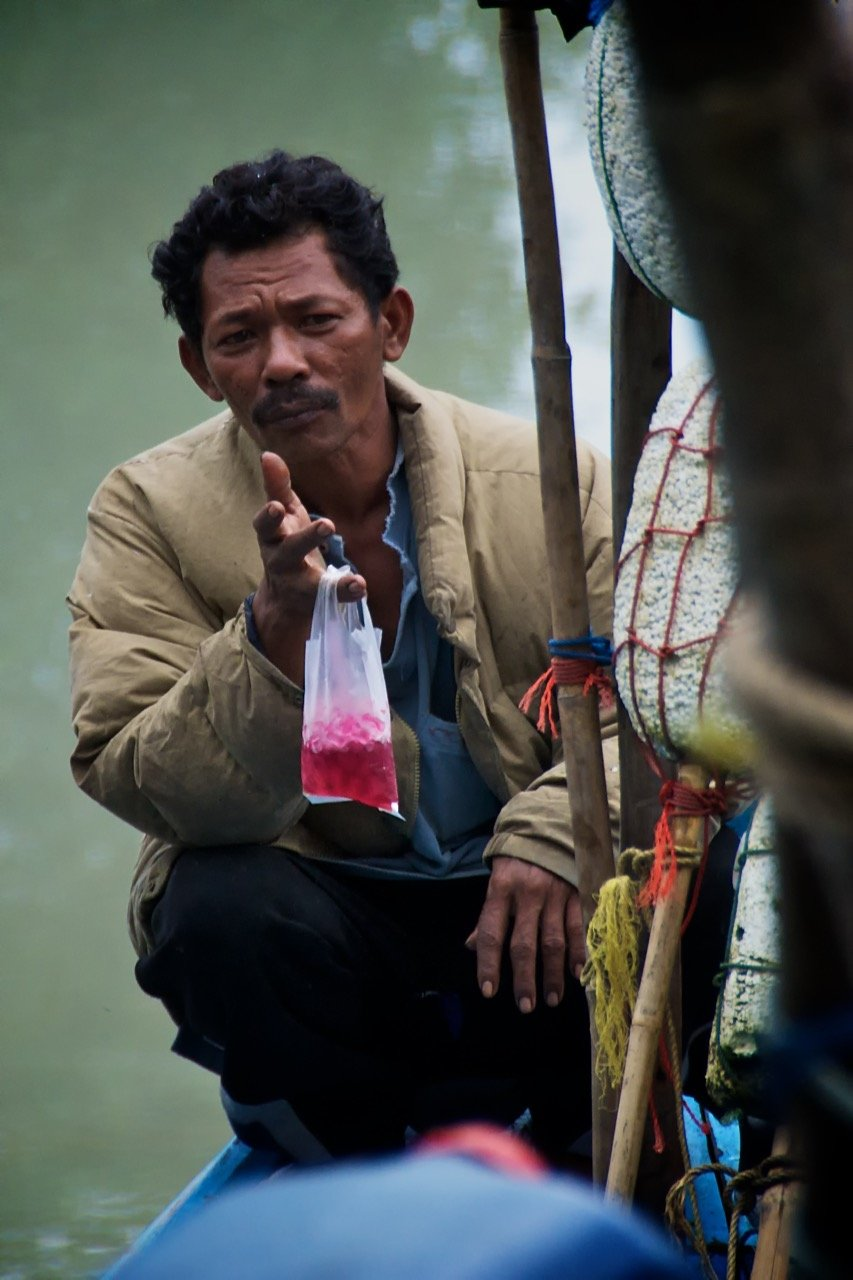 A local fishermen enjoys a Thai snack as he prepares to head out to sea. The mariners rely on the sea for their livelihoods, their traditions and their very existence.