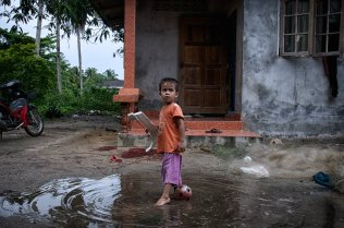 The children of Tha Sala have the most to lose as traditions give way to development from the government and big industry. Here, a nephew of Manit Hankla plays in the rainwater in the family's humble compound. While too young to work on the boat, if the power plant is completed, it's unclear what his future will hold.