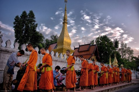 Monks collect donations at dawn in Luangprabang, Laos, on Oct. 9, 2012. The traditions of Theravada Buddhism remain strong here despite the communist government's official stance against religion. It seems tourism dollars can be more important than ideology.