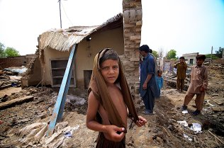 On Friday, Sept 3, 2009, a boy stands outside a house destroyed by flood waters that swept through Mehmood Kot a month ago. Residents of Mehmood Kot have been waiting a month for relief aid, which they say they have not receieved.