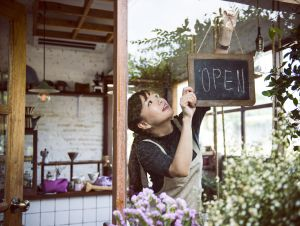 """Small business owner putting """"Open"""" sign in floral shop window"""