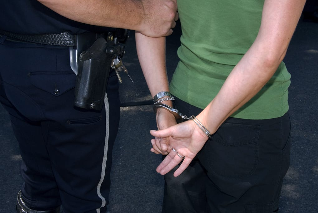 Young person in handcuffs being escorted by a police officer