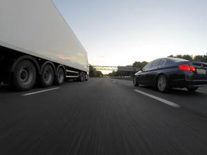 Photo of a semi truck passing a sedan on the highway