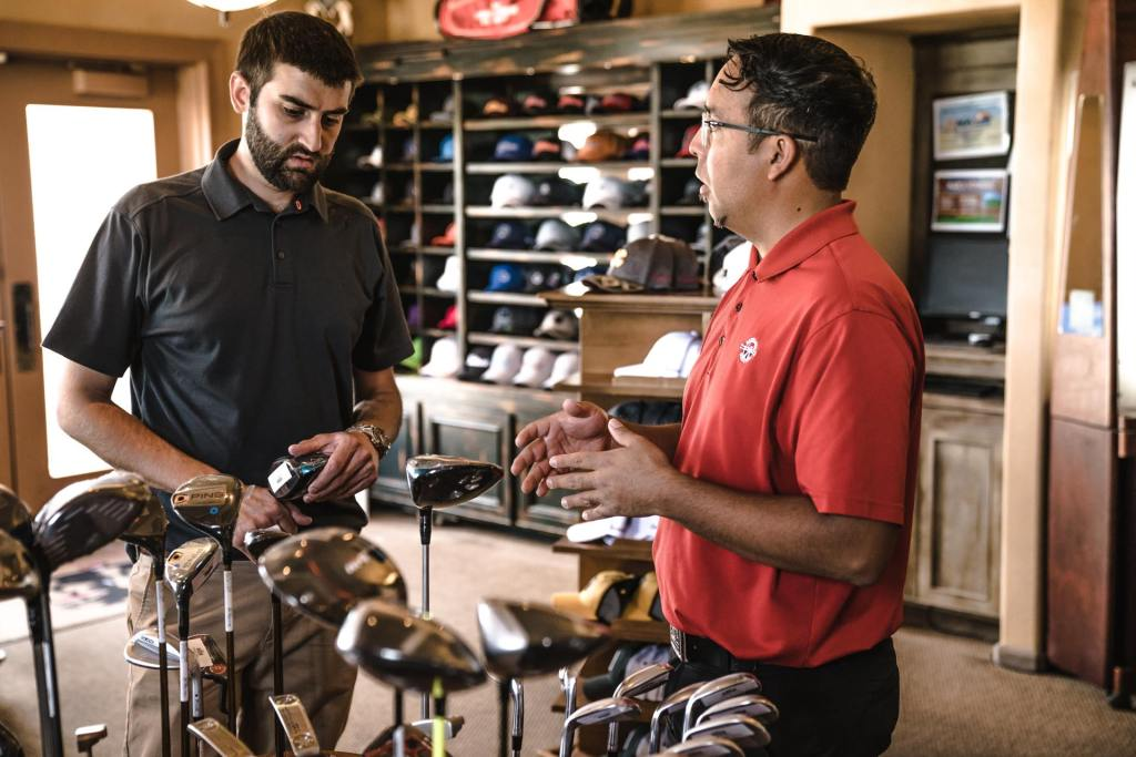 A sporting goods franchise owner speaks with a customer about golf clubs.