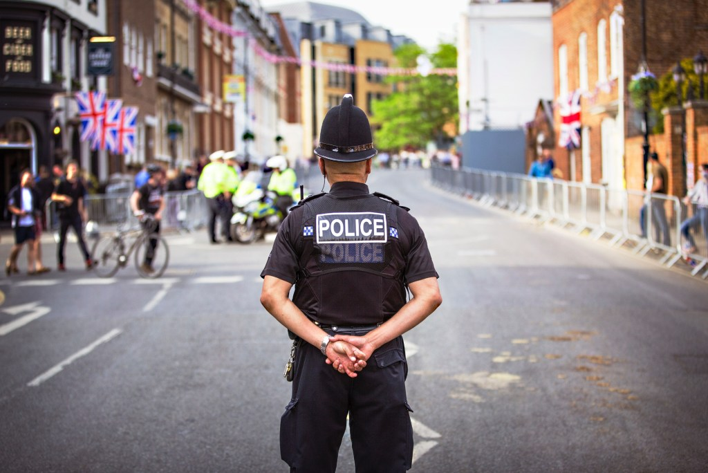 British Police officer protecting the neighborhood. Photo by King's Church International on Unsplash.
