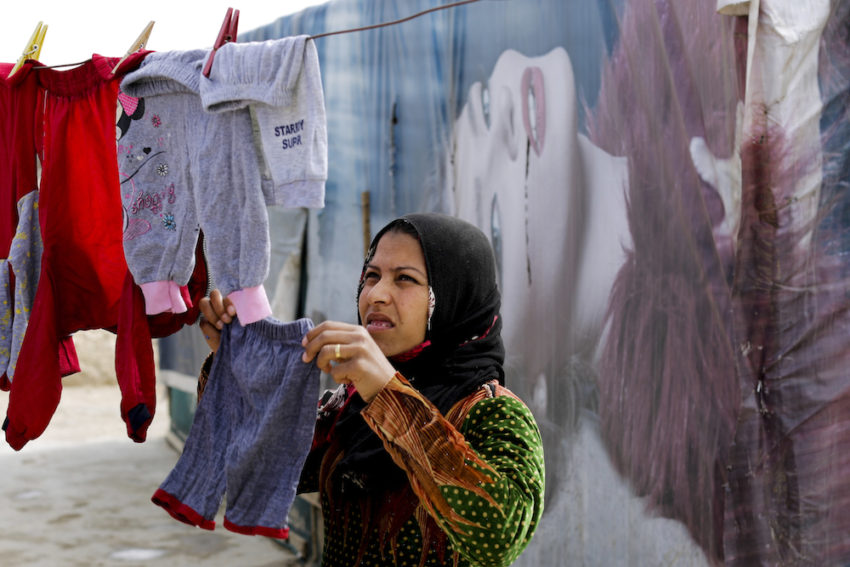 A Syrian refugee hanging her laundry at an informal refugee camp in Lebanon's Bekaa Valley. (Hassan Ammar / AP)