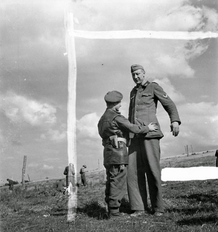 One Canadian soldier with hostage Jacob Nacken, the tallest soldier of the German army, in Calais, 1944
