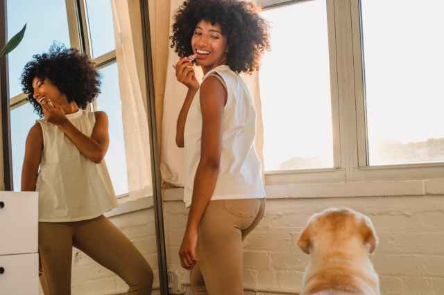 content black woman reflecting in mirror near purebred dog