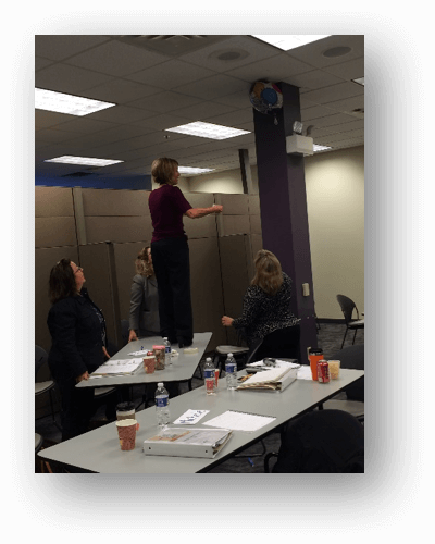 A woman standing on a desk participating in experiential learning.