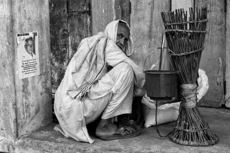 Man Crouched Down on Streets on Varanasi in Black and White - Varanasi, India - Copyright 2016 Ralph Velasco