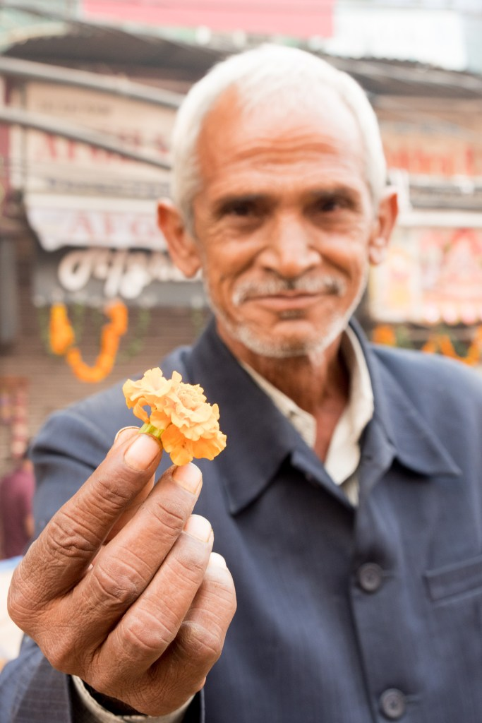 Man Offering Me Marigold at Spice Market - Old Delhi, India - Copyright 2016 Ralph Velasco