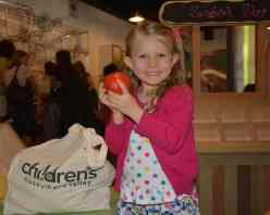 Girl with apple at Children's Museum Oro Valley