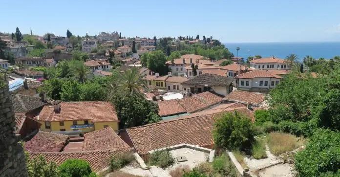 Blick über die Dächer der mit roten Ziegeln gedeckten Dächer von Antalyas Altstadt aufs Meer hinaus.