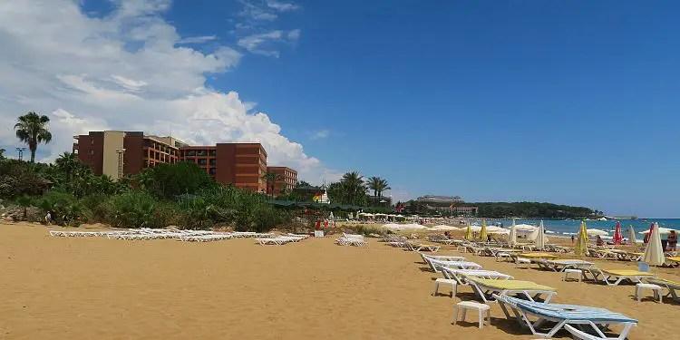Ein Hotel und Liegestühle am Meer.