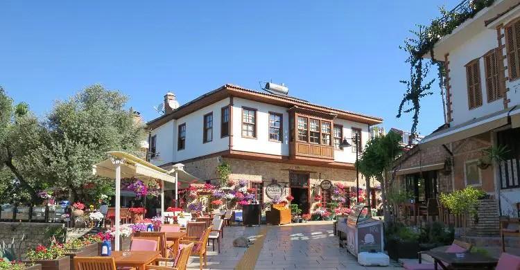 Das Odile Hotel mit seinem roten Ziegeldach und dem kleinen Gastgarten davor mit vielen kleinen Holztischen.