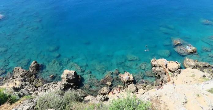 Ein schmaler Weg führt die 40 Meter hohen Klippen hinunter. Das Foto ist von der oberen Seite des Weges aufgenommen worden. Darunter ist da türkislblaue Meereswasser zu sehen. Darin schwimmen ein paar Kinder.