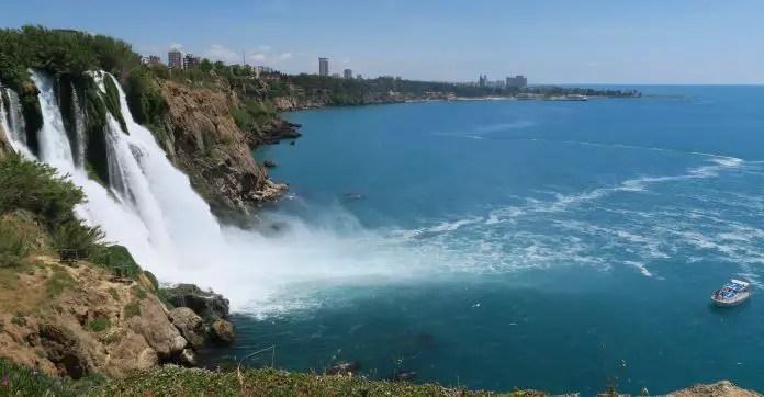Der Düden Wasserfall stürzt 40 Meter hohe Klippen ins Meer hinab. Am Meer ist neben dem Wasserfall ein weißes Boot zu sehen. Ein Angler steht neben dem Wasserfall. Das Foto ist von den Klippen aus aufgenommen worden.