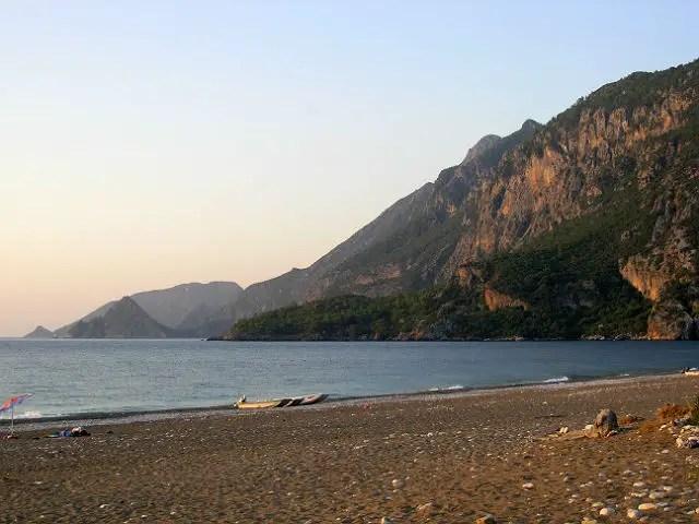 Olympos Beach am Abend bei Sonnenuntergang. Es sind keine Touristen mehr am Strand zu sehen. Der Blick geht auf das Meer und auf der rechten Seite gelegene Hügel mit Pinienwälder hinauf.