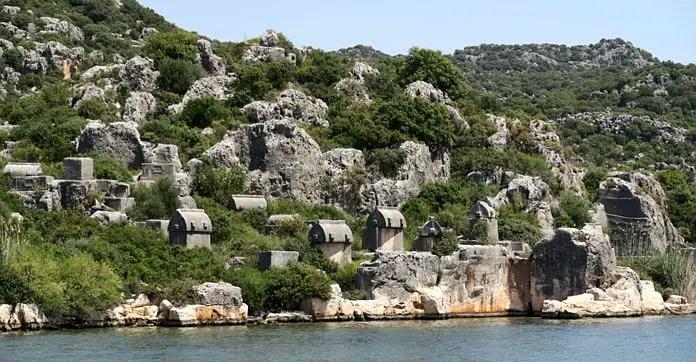 Lykische Steinsarkophage stehen an der Küste von Ücagiz am Meer auf einem kleinen grün bewachsenen Hügel.