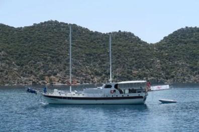 Eine weiße Segelyacht mit zwei Masten ist vor der Insel Kekova zu sehen.