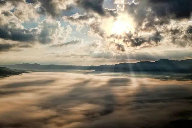 Blick auf eine dichte Wolkendecke von einem Flugzeug aus gesehen. Am Horizont ist die untergehende Sonne zu sehen.