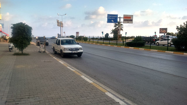 Straßenkreuzung in Alanya. Ein weißes Auto steht neben der Straße