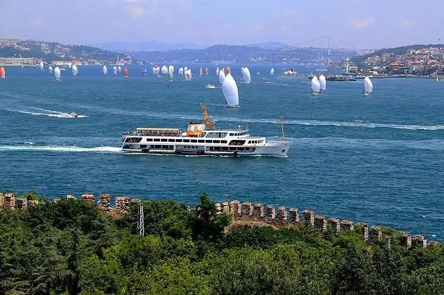 Viele kleine Segelschiffe am Bosporus in Istanbul. Im Vordergrund ist eine Stadtmauer und eine große Fähre zu sehen.