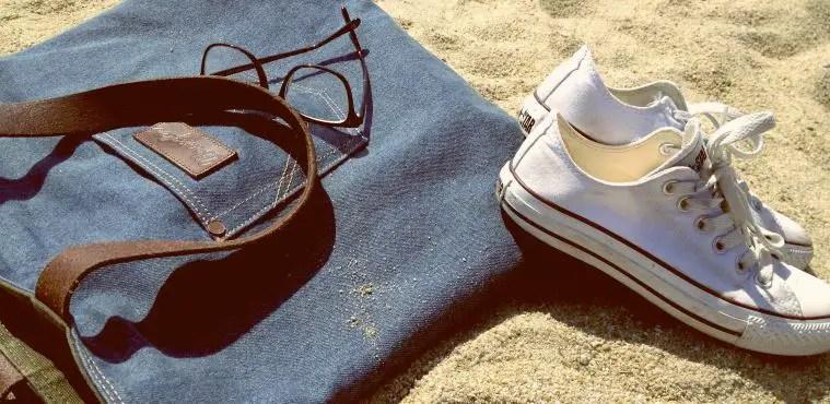 Strandtasche aus blau gefärbten Jeansstoff, weiße Converse Schuhe und einen optische Brille mit einem schwarzen Rahmen von Ray Ban