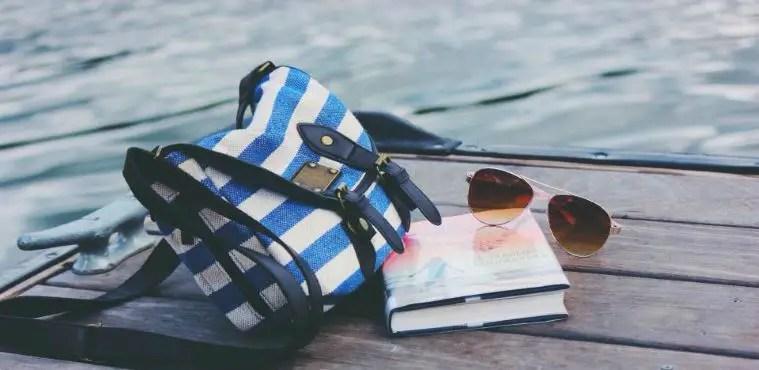 Blau-Weiß gestreifte Tasche mit schwarzen Lederriemen, ein Buch und eine Ray Ban Sonnenbrille liegen auf einem Holztisch am Strand