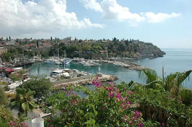 Blick auf den Yachthafen und die Altstadt Anatalyas, Kaleice, von einer gegenüberliegenden Klippe. Es sind Schiffe im Hafen, die alten Hafenmauern der Stadt und die grün bewachsenen Parks zu sehen.