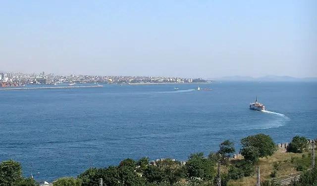 Blick von einer Terasse des Topkapi Palast auf den Bosporus und das Maramarameer in Istanbul. Ein Teil der gegenüberliegenden Landseite von Istanbul ist zu sehen. Am Bosporus ist ein kleines Schiff zu sehen.