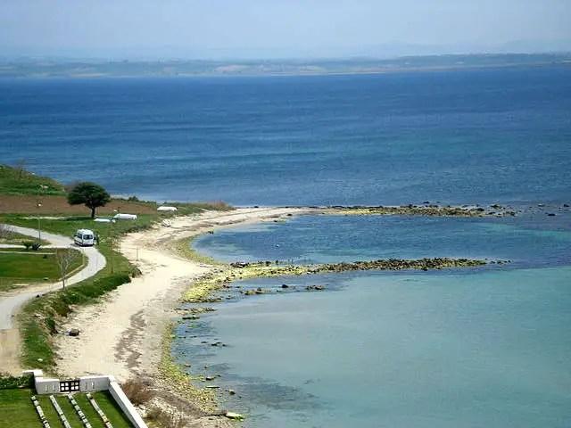 Meeresbucht in den Dardanellen. Die Küste ist fach. Es gibt einen kleinen Sandstrand. Das Meer ist dunkelbau gefärbt. Das Ufer ist grün bewachsen.