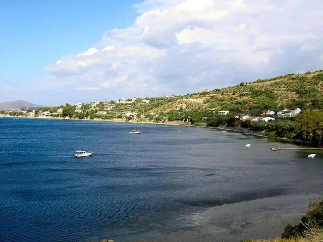 Eine Bucht mit dunkelbauen Wasser ohne einen Sandstrand. Die Küste fällt relativ steil ab. Am Meer sind ein paar kleine Boote zu sehen. Es ist Tag. Auf der rechten Bildseite ist trotz Sonnenscheins eine große Wolke zu sehen.