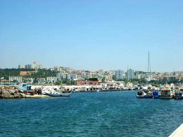 Einfahrt in den Hafen von Canakkale. Des Meereswasser ist dunkelblau. Es sind viele Schiffe im Hafen zu sehen. Das Bild ist von einem Boot aufgenommen worden.