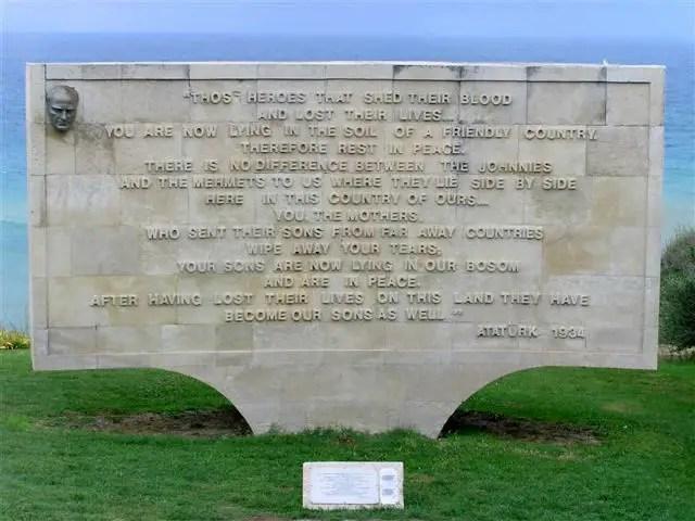 Gedenktafel mit einer Inschrift von Mustafa Kemal Atatürk an die gefallenen Soldaten in Gallipoli. Der genaue Inhalt ist auf dem Foto nicht erkennbar. Im Hintergrund ist das Meer zu sehen.