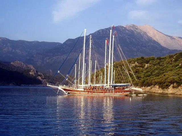Ein Gulet ist ein türkisches Segelschiff. Es ist aus Holz gebaut. Die Masten sind weiß. Die Farbe der Segel ist nicht zu erkennen, weil sie eingerollt sind. Das Bild ist von einem anderen Schiff aufgenommen worden. Davor ist das blaue Wasser des Mittelmeeres zu sehen. Im Hintergrund befinden sich die hohen Berge des Taurusgebirges