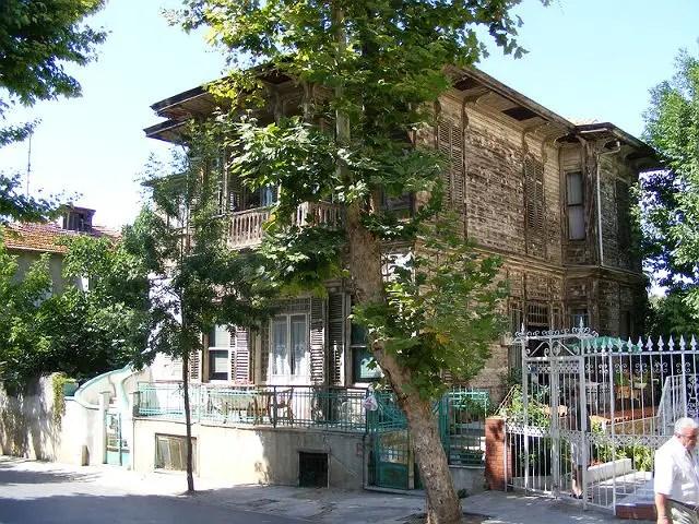 Haus auf der Insel Büyekada. Davor steht ein grüner Laubbaum. Die fabre des Hauses ist in heller Holzfarbe gehalten. Es ist zwei Stokwerke hoch und hat ein flaches Dach.